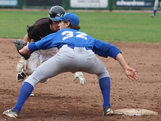 Catholic Central first baseman Nick Sykyes (32) is about the catch the ball and tag our Rice runner Kevin Tyranski on a fifth-inning pick-off play.