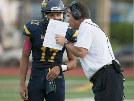 Naples head coach Bill Kramer gives a play to quarterback