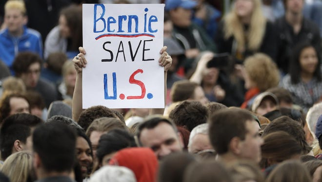 A supporter of Democratic presidential candidate Sen. Bernie Sanders, I-Vt., holds up a sign before a campaign rally Tuesday, May 3, 2016, in Louisville, Ky.