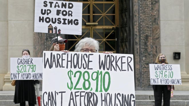 Advocates for low-wage workers demonstrate at City Hall on Thursday, calling for more affordable housing and assistance for those facing eviction due to the coronavirus pandemic.