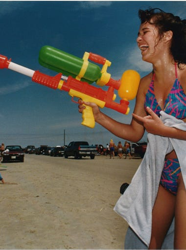 Jennifer Vaughn, sophomore at Carroll High School, celebrates spring break with a Super Soaker water gun at J.P. Luby Surf Park March 18, 1993, as Alanna Martinez looks on.