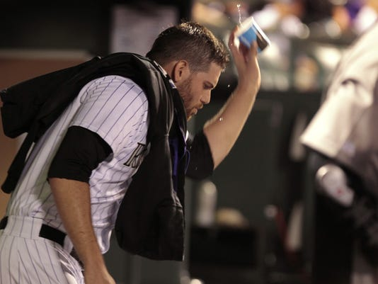 Colorado Rockies relief pitcher Adam Ottavino throws a cup of water in the dugout after leaving the baseball game against the Chicago Cubs in the 11th inning in Denver on Tuesday, Aug. 5, 2014. (AP Photo/Joe Mahoney)
