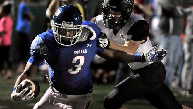 Cooper Cougars running back Tyrees Whitfield fends off Lubbock Cooper defensive back Payton Bourquin before crossing the goal line for a touchdown Friday at Shotwell Stadium. Cooper beat Lubbock Cooper, 52-14.