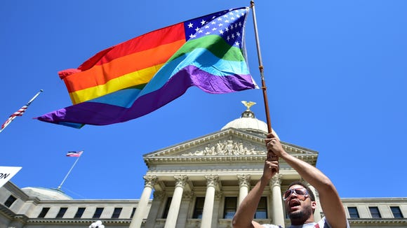 Meridian resident Nykolas Alford waves a rainbow-colored American flag on the Capitol steps March 29 during a Human Rights Campaign protest of House Bill 1523, which critics call discriminatory.