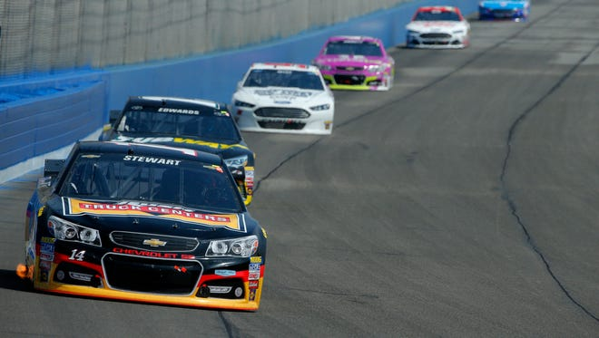 Tony Stewart, leading a pack of cars during Sunday's Auto Club 400, finished 14th for his best result of the season.