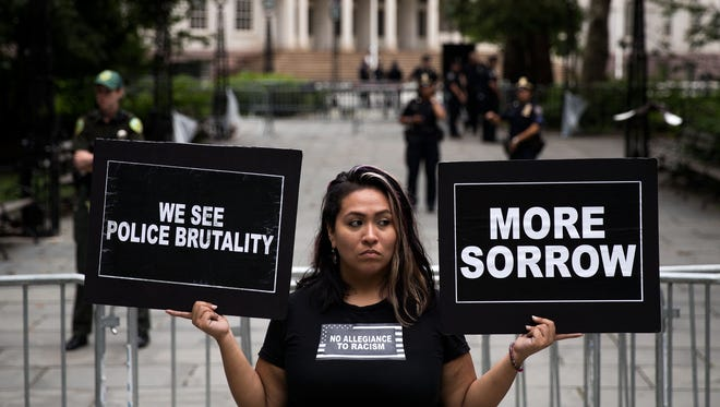 Lorena Ambrosio, of New York, holds up signs during a protest against police brutality at City Hall Park.