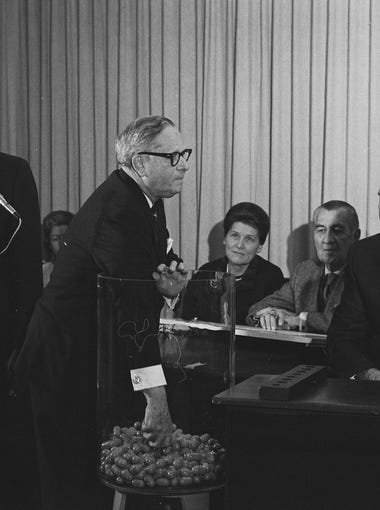 New York Congressman Alexander Pirnie reachesinto a container of draft numbers as others watch at the Selective Service Headquarters during the nationwide draft lottery on Dec, 1, 1969.