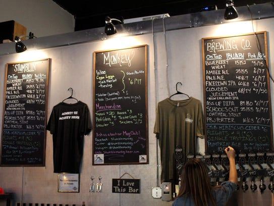 Holly Miller updates the beer menu at Stumblin' Monkey