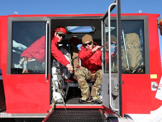 Rescuers depart Timberline Lodge in a snow tractor