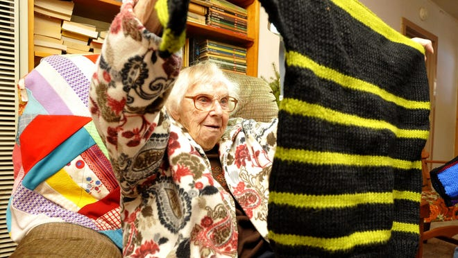 """Edwina """"Larry"""" Knowles shows off a sweater she knitted. At 100 years of age, Knowles still lived an independent life at her Niehart ranch, once home to the popular Sun Mountain Ranch sledding area and a boys' camp."""