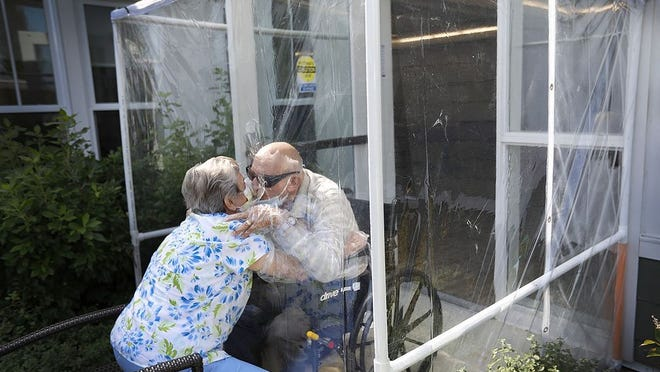 Maryann Salvatore kisses her husband Mario through the protective plastic on Thursday Sept. 24, 2020. They have been married 68 years and are from Quincy. Greg Derr/ The Patriot Ledger