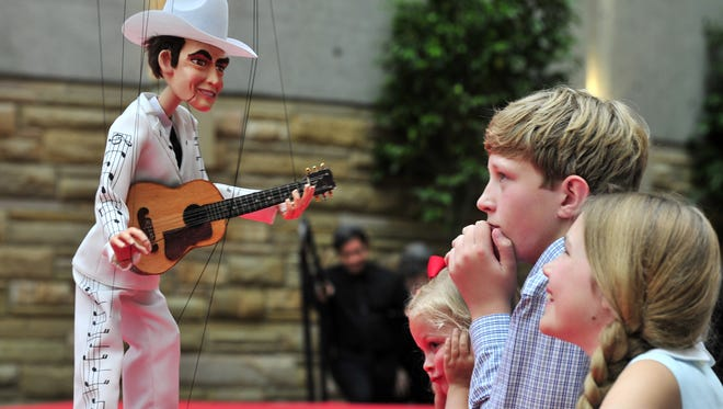 Hank Williams greets Mary Evans Bumstead, 4, left, Bass Bumstead,13, and Merrill Bumstead, 11, during a promenade before the debut of the String City puppet show at the Country Music Hall of Fame and Museum on June 11,  2013.