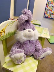 A stuffed rabbit rests on one of two chairs in one
