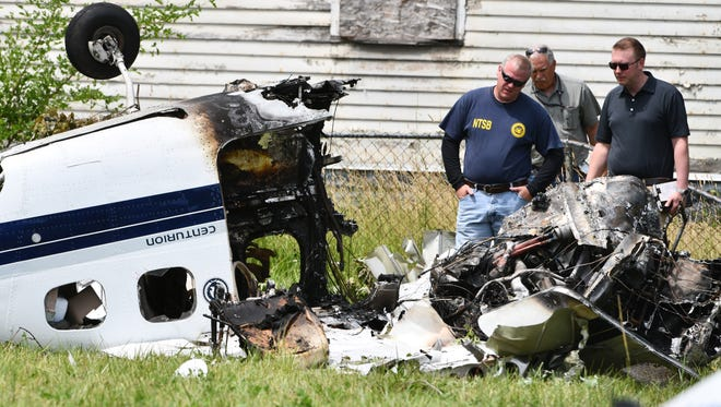 NTSB agents work at the site of a small-plane crash in a field on Milton, west of Van Dyke in Detroit on Monday.