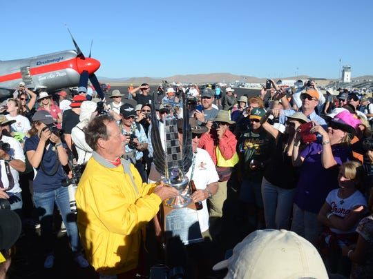 """Robert """"Hoot"""" Gibson holds up his first place trophy after winning the Breitling Unlimited Gold on Sunday at the Reno National Championship Air Races."""