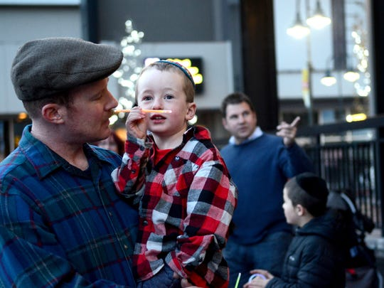 Reno resident Joe Gorman, 35, holds his 4-year-old son, Moses, on Sunday just before the annual lighting of the giant menorah at Reno City Hall.