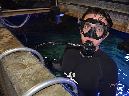 James Hill, aquarist at the Mississippi Museum of Natural Science, poses for a photo before entering the waters of the aquarium to feed various living species.