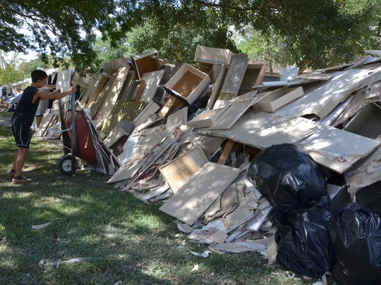 Nick Heston, 13 dumps a load of sheetrock and insulation at the road in front of a friends house in Baton Rouge on August 20, 2016.   [Via MerlinFTP Drop]