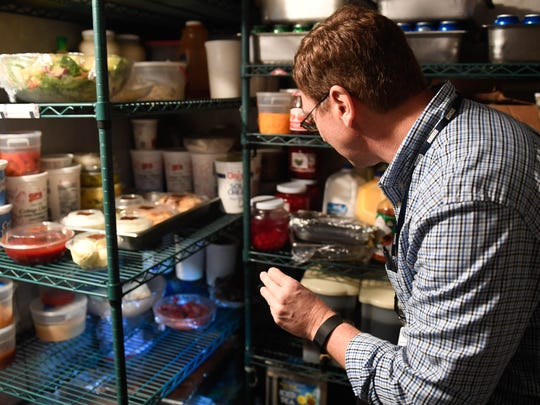 Vanderburgh County Health Department restaurant inspector Chris Borowiecki checks the food storage in a walk-in cooler at the Bauerhaus on Darmstadt Road Monday, October 31, 2016.