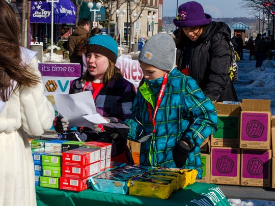 Girl Scouts are shown selling cookies.