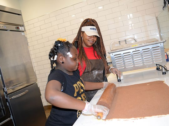 As part of the Junior Girls Day Out, April McGee, manager of Cinnabon located in Northpark Mall, shows Kamya Sorrell, 9 of Jackson how to make cinnamon rolls.