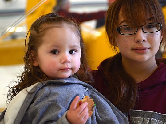 Esperanza Correa, 16, holds her little sister, Ariah, 1, as they pose for a photo during the Operation Santa Claus charity event held on Dec. 9, 2017 and organized by The Children's Cabinet and the Reno-Tahoe Airport Authority.