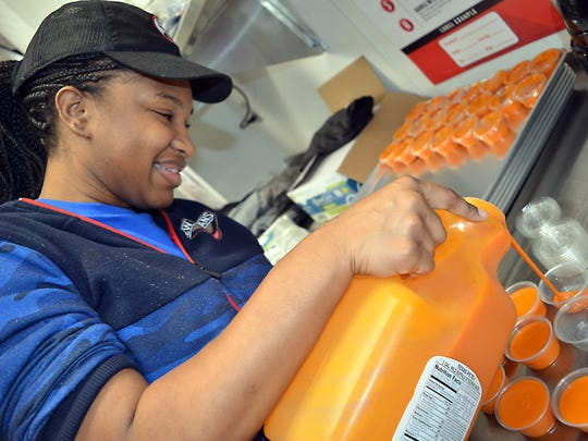 Charniette Walker fills containers with buffalo sauce