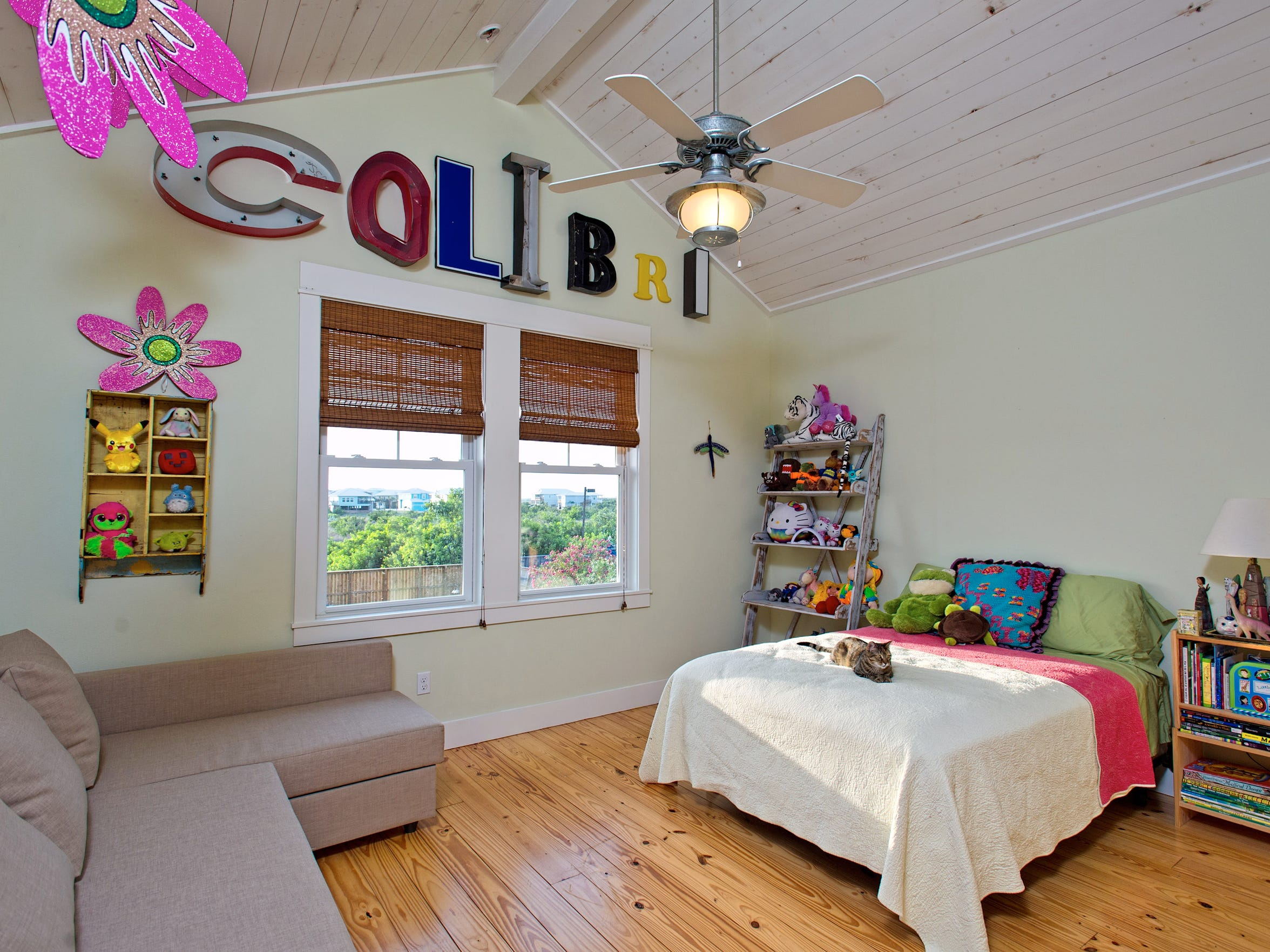 A spacious bedroom with knotty pine plank flooring and a cathedral wood plank ceiling