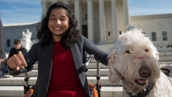 FILE - In this Oct. 31, 2016 file photo, Ehlena Fry of Michigan, sits with her service dog Wonder, while speaking to reporters outside the Supreme Court in Washington. The Supreme Court says a lower court should take another look at whether Fry, who has cerebral palsy can sue Michigan school officials over their refusal to let her to bring a service dog to class.