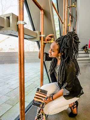 "Everett student Jeanne Murekatete listens to her voice read an essay from a faucet at the 'Beyond Streaming-A Sound Mural for Flint"" exhibit Saturday January 21, 2017 at the Broad Art Musuem in East Lansing.  KEVIN W. FOWLER PHOTO"