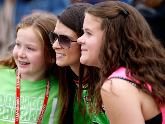 Danica Patrick, driver of the #7 GoDaddy.com Chevrolet, poses with two fans during qualifying for the NASCAR Nationwide Series F.W. Webb 200 at New Hampshire Motor Speedway on July 14, 2012 in Loudon, New Hampshire.