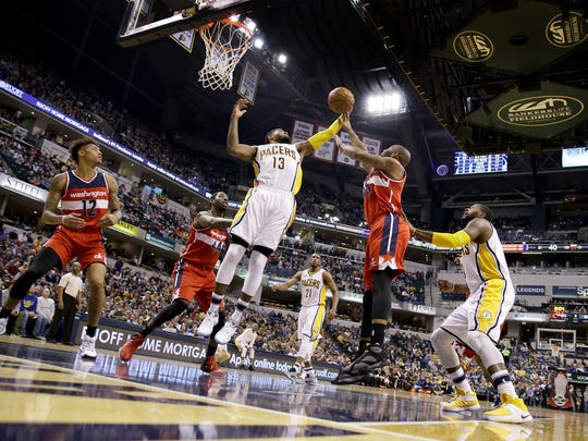 Pacers forward Paul George (13) pulled in a rebound over Washington Wizards guard Marcus Thornton (15) in the first half of their game Monday.