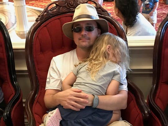 Daddy Duty columnist Tim Walters holds daughter Isabella as she naps before lunch at Disney's Magic Kingdom.