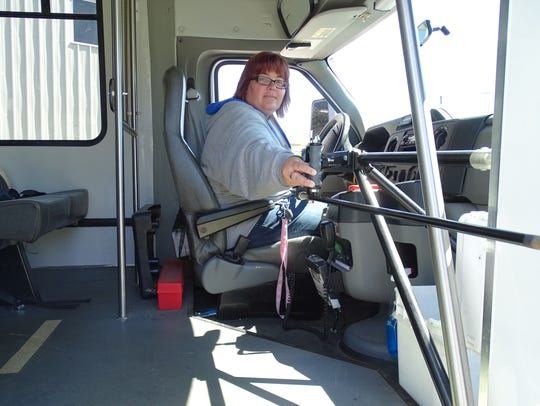 Beth Rickard, safety manager of SCAT, holds open the