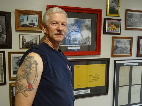 Gordon Grove shows off his tattoo while standing next to photos of the most memorable day he had with the fire department.