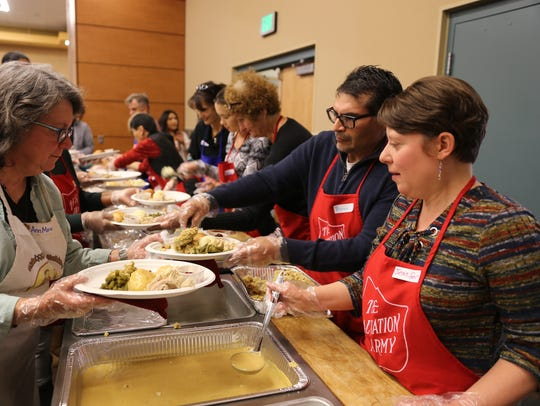 Ann McCarthy, left, holds a plate of food as Bryan Salazer and Jennifer Salazer dish out stuffing and gravy during the Salvation Army Thanksgiving meal on Thursday at the Farmington Civic Center.