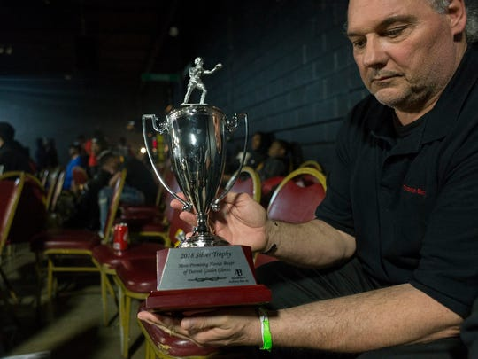 Ken Fischer, owner of Throwback Boxing, holds up the Silver Trophy on Sunday at Bert's Warehouse Theater in Detroit.