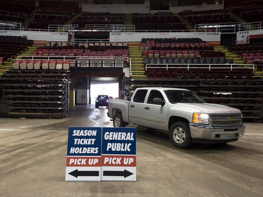 Cars drive through the Joe Louis Arena to pick up stadium