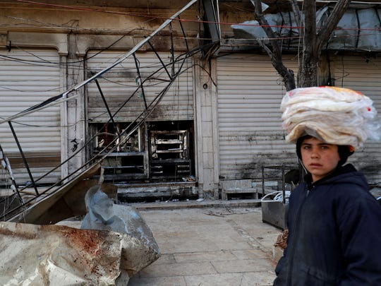 "A boy walks past the site of a suicide attack targeting US-led coalition forces in the flashpoint northern Syrian city of Manbij which killed four US servicemen on Jan. 17, 2019.  The bombing, claimed by the Islamic State group, comes after President Trump's announcement last month that he was ordering a full troop withdrawal from Syria because the jihadists had been ""largely defeated."""