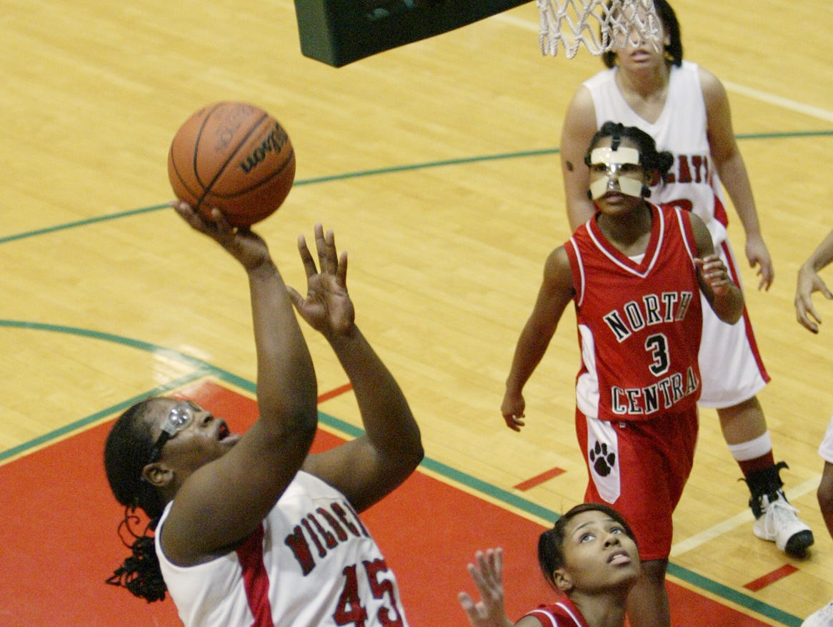 FILE – Lawrence North's Felisha Johnson (45) goes to the basket over North Central's Jalen Greene (34) and Kira Carter (35) in 2008.