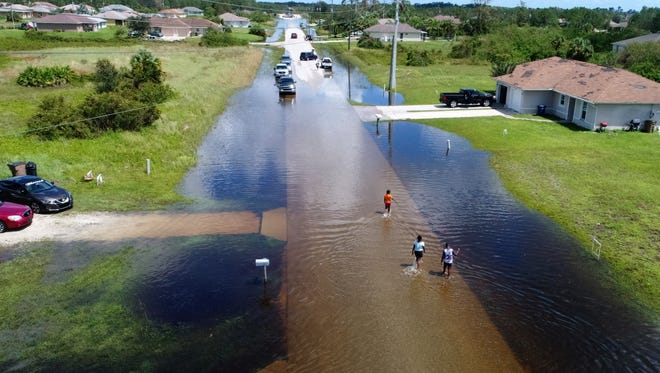 Children walk through flooded streets Tuesday, Sept. 12, 2017, two days after hurricane Irma passed through the Lehigh Acres area outside Fort Myers, Fla.