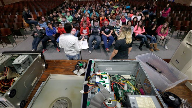 Mikki Halbach (left), co-owner of Pilgram Recycling, and employee Laura Bartlett talk to students about the importance of recycling electronics recently at Roosevelt Middle School in Appleton.