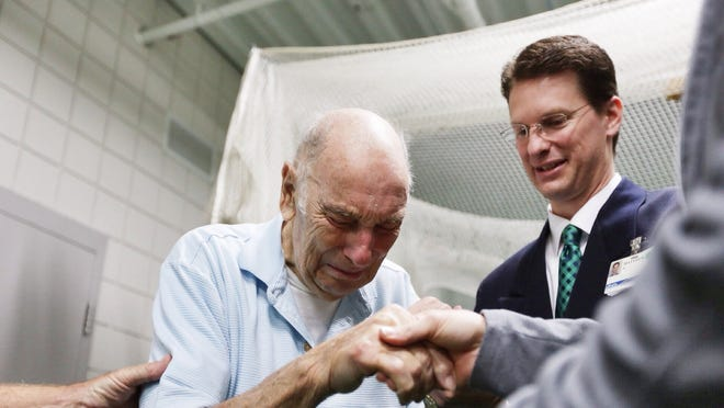 Warren resident 94-year-old Sam Aliotta holds the hand of Henry Ford Health System exercise physiologist Sheryl Sebastian while meeting her and Henry Ford Health System exercise physiologist Matthew Saval for the first time on Wednesday, Sept. 17, 2014, at the Henry Ford Health Systems William Clay Ford Center for Athletic Medicine in Detroit. Aliotta was facing sudden cardiac death as a result of his heart beating out of control on a Sept. 6 flight into Detroit and was saved by the two Henry Ford Health System Cardiac Rehabilitation exercise physiologists.