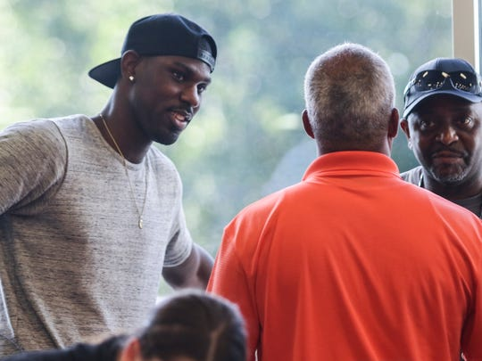 Alex Poythress, Northeast High School alumnus and former Kentucky basketball player, left, speaks with Josh Artis' father, Mike Artis, center, during a basketball court dedication in Josh Artis' memory in July 2016 at Clarksville Athletic Club.