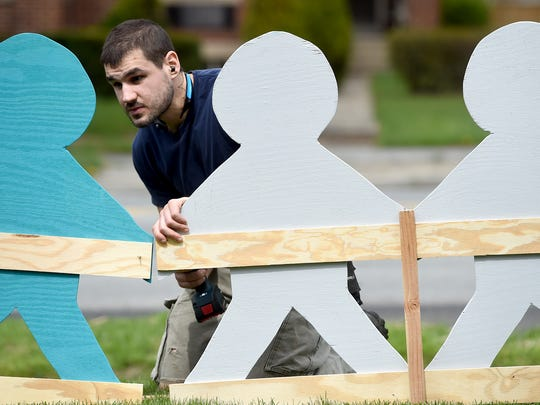 Jordan Tolman, a volunteer with Turning Point Women's Counseling & Advocacy Center helps put together a display on the front lawn of the center. A group of clinicians and volunteers helped get the project finished.
