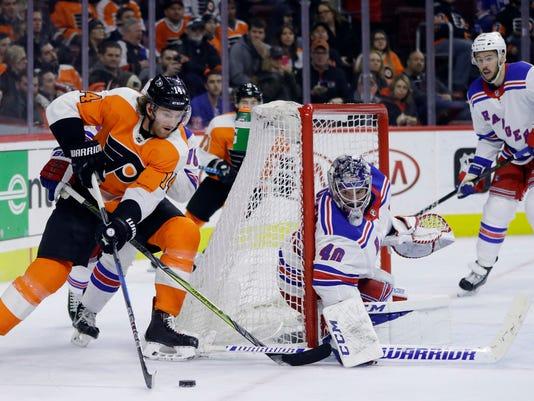 Philadelphia Flyers' Sean Couturier, left, tries to get a shot past New York Rangers' Alexandar Georgiev during the second period of an NHL hockey game, Thursday, March 22, 2018, in Philadelphia. (AP Photo/Matt Slocum)
