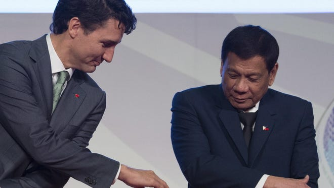 Canadian Prime Minister Justin Trudeau, center, shakes hands with Philippine President Rodrigo Duterte during a photo session of the ASEAN-Canada 40th Commemorative session in Manila, Philippines, Tuesday, Nov. 14, 2017.
