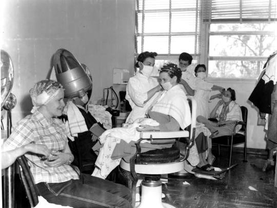 A black and white of W.T. Edwards patients in the hospital hair salon; note the masks to keep the stylists from breathing infectious air.