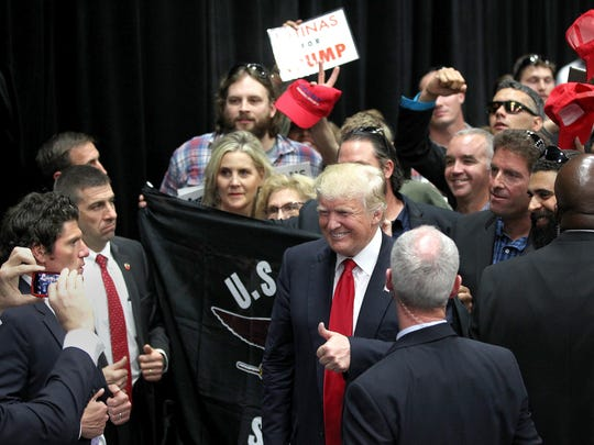 Donald Trump smiles for one last photo at the San Diego Convention Center  before leaving behind the black curtain at left after his two-city California tour from Fresno to San Diego Friday, May 27, 2016.  Donald Trump greets the crowd after speaking to his supporters at the San Diego Convention Center on Friday, May 27, 2016.