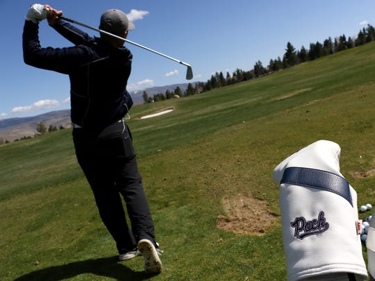 Nevada's Sam Harned watches his ball as the golf team